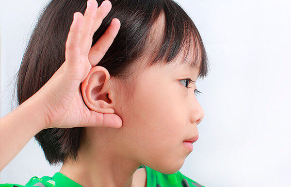 Niño mostrando su orejas tras postoperatorio de otoplastia